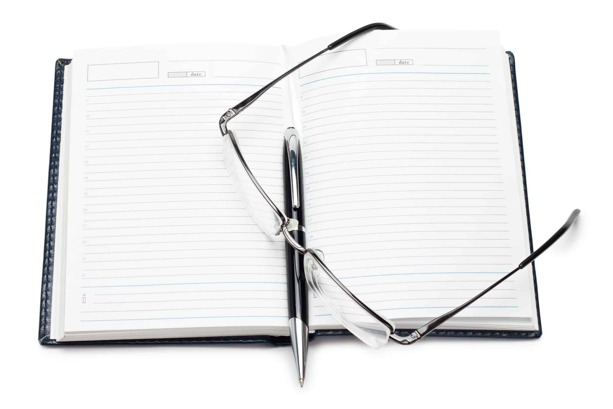 Opened Notebook With Pen And Glasses Isolated