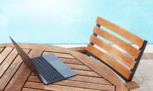 Laptop on table near swimming pool